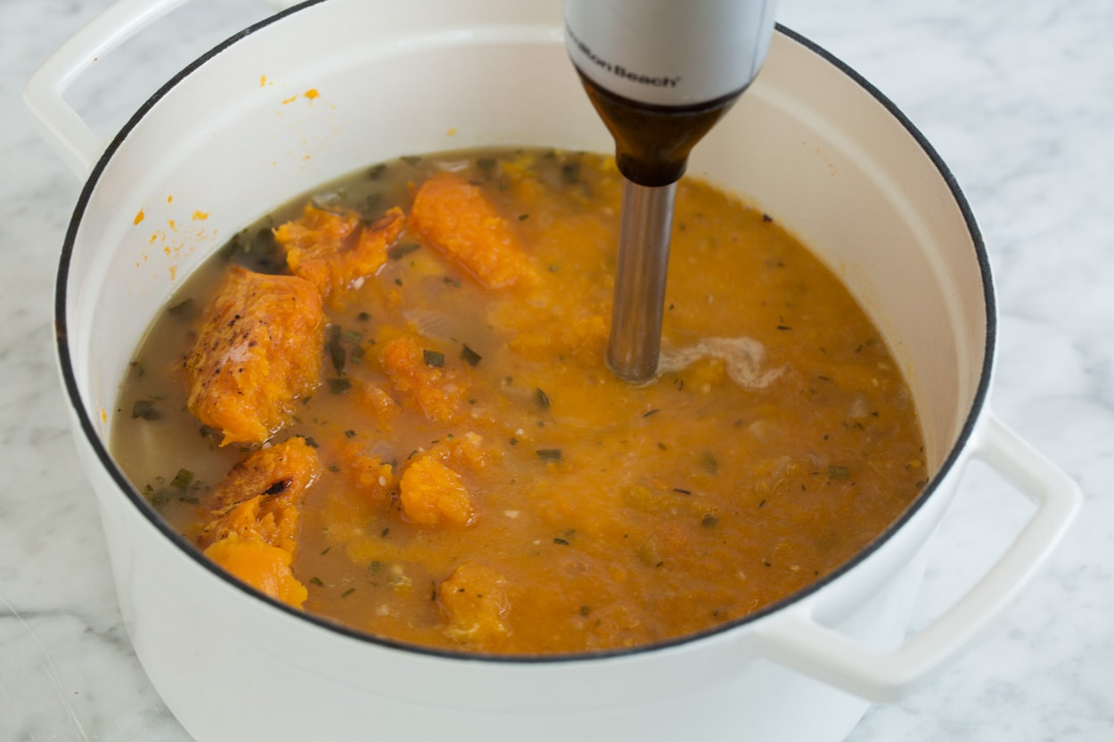 Shown here blending roasted squash into soup mixture in pot with an immersion blender for butternut squash soup