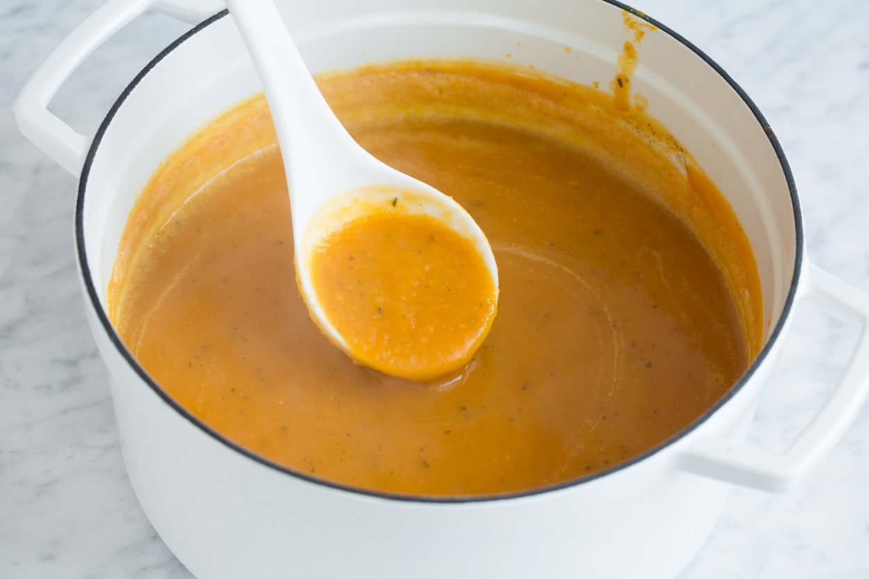 Finished butternut squash soup shown here in enameled white pot