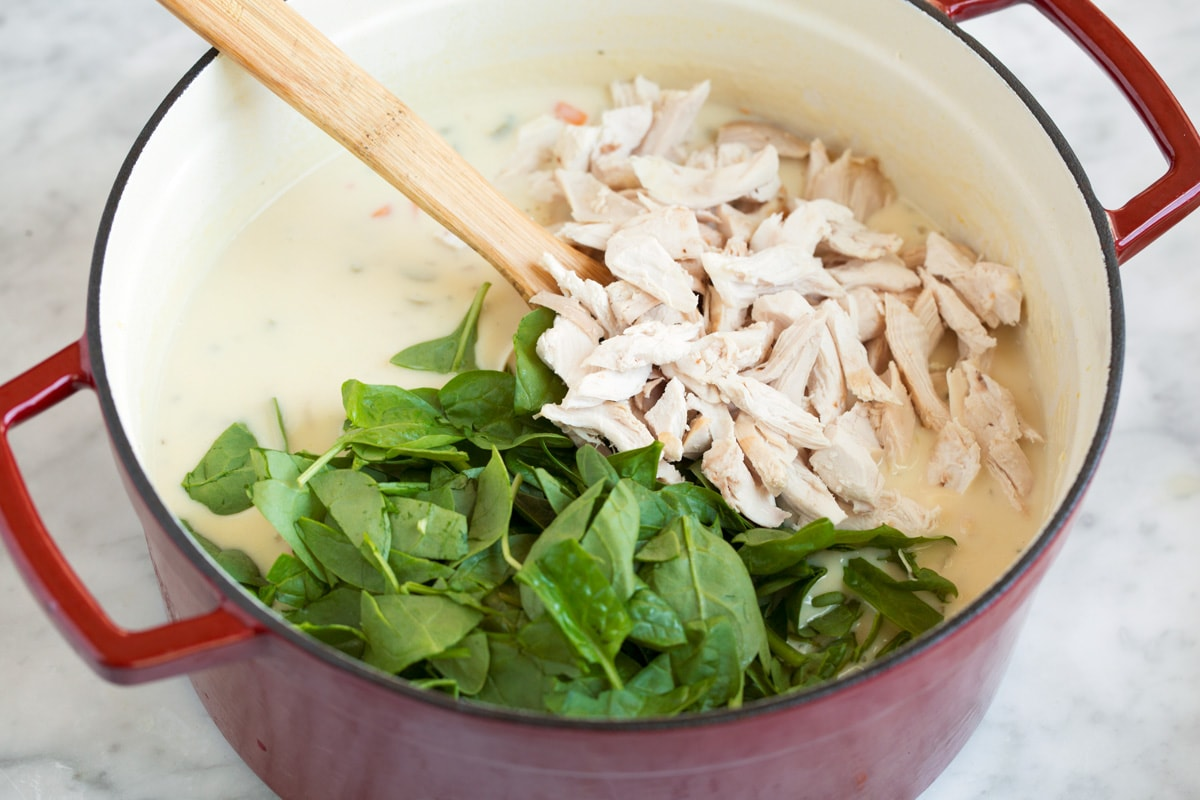 Adding cooked shredded chicken and spinach to pot.
