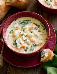 Serving of creamy chicken gnocchi soup in a red soup bowl.