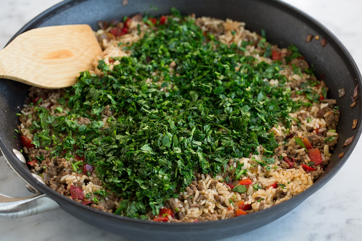 Adding parsley and cilantro to Chimichurri Beef and Rice after cooking.