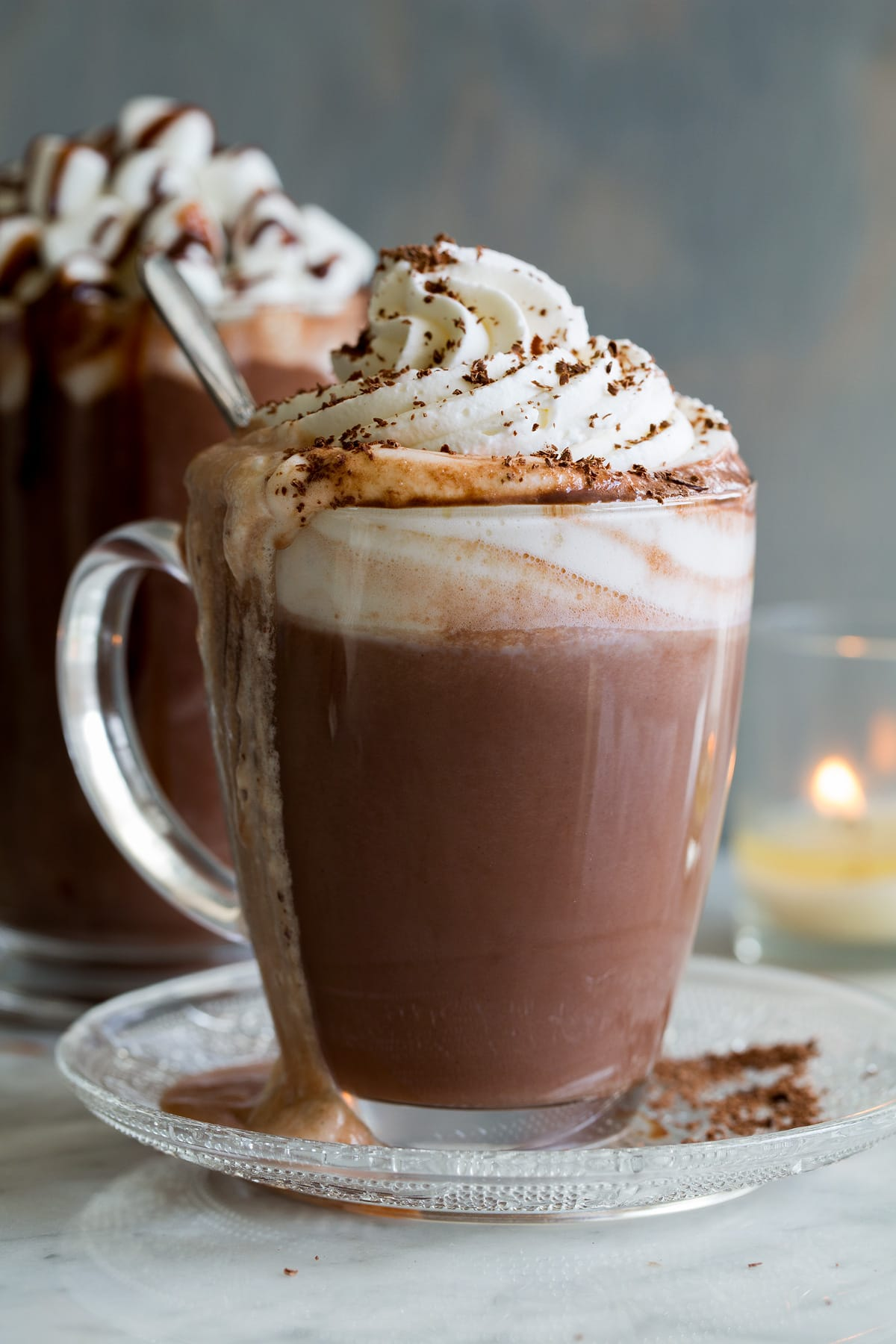 Hot Chocolate shown here in a glass mug with whipped cream and chocolate shavings on top