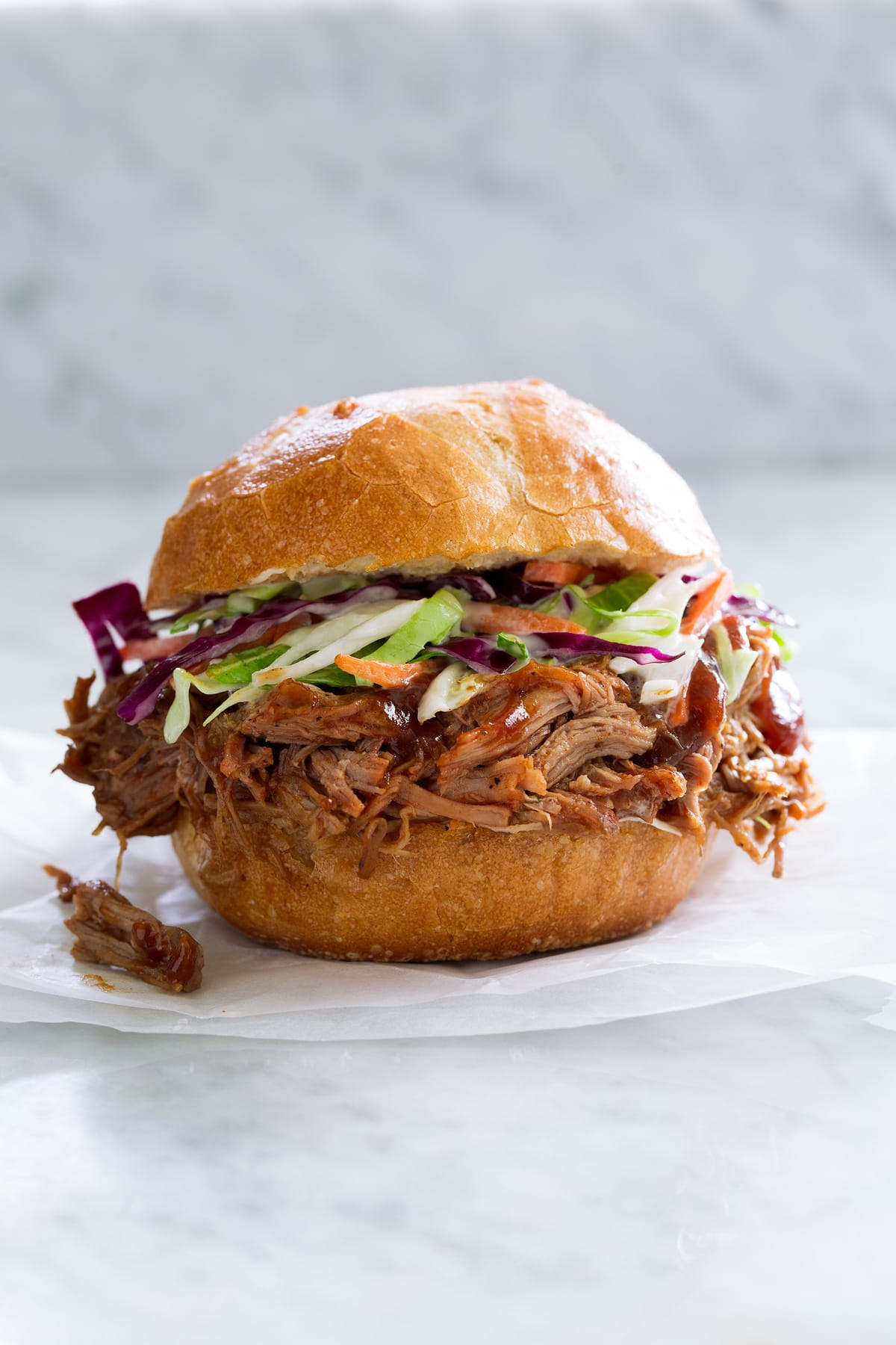 Pulled Pork shown here in a bun with coleslaw sitting on parchment paper on a marble surface