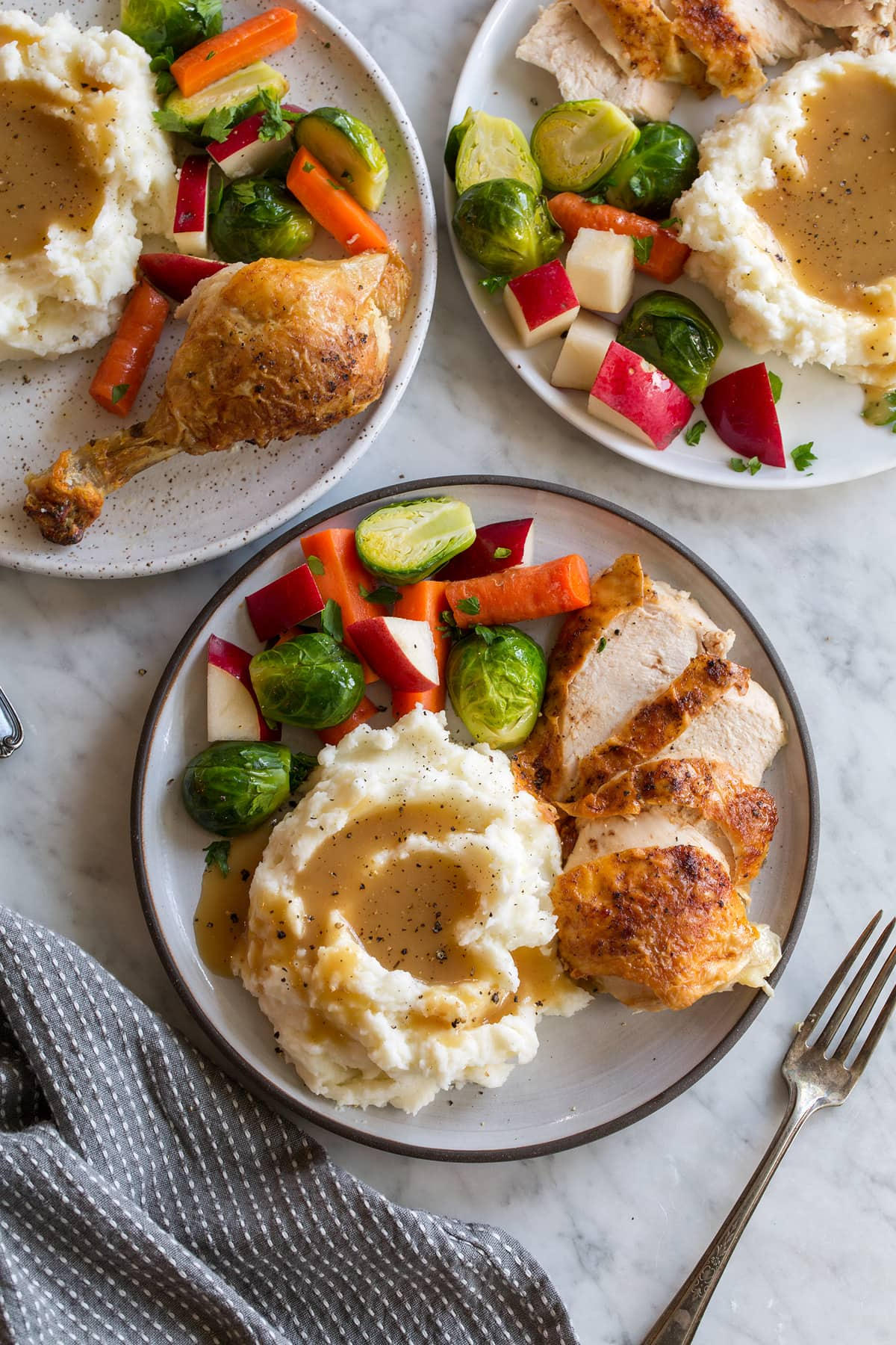 Roast chicken with mashed potatoes, gravy, and steamed veggies.