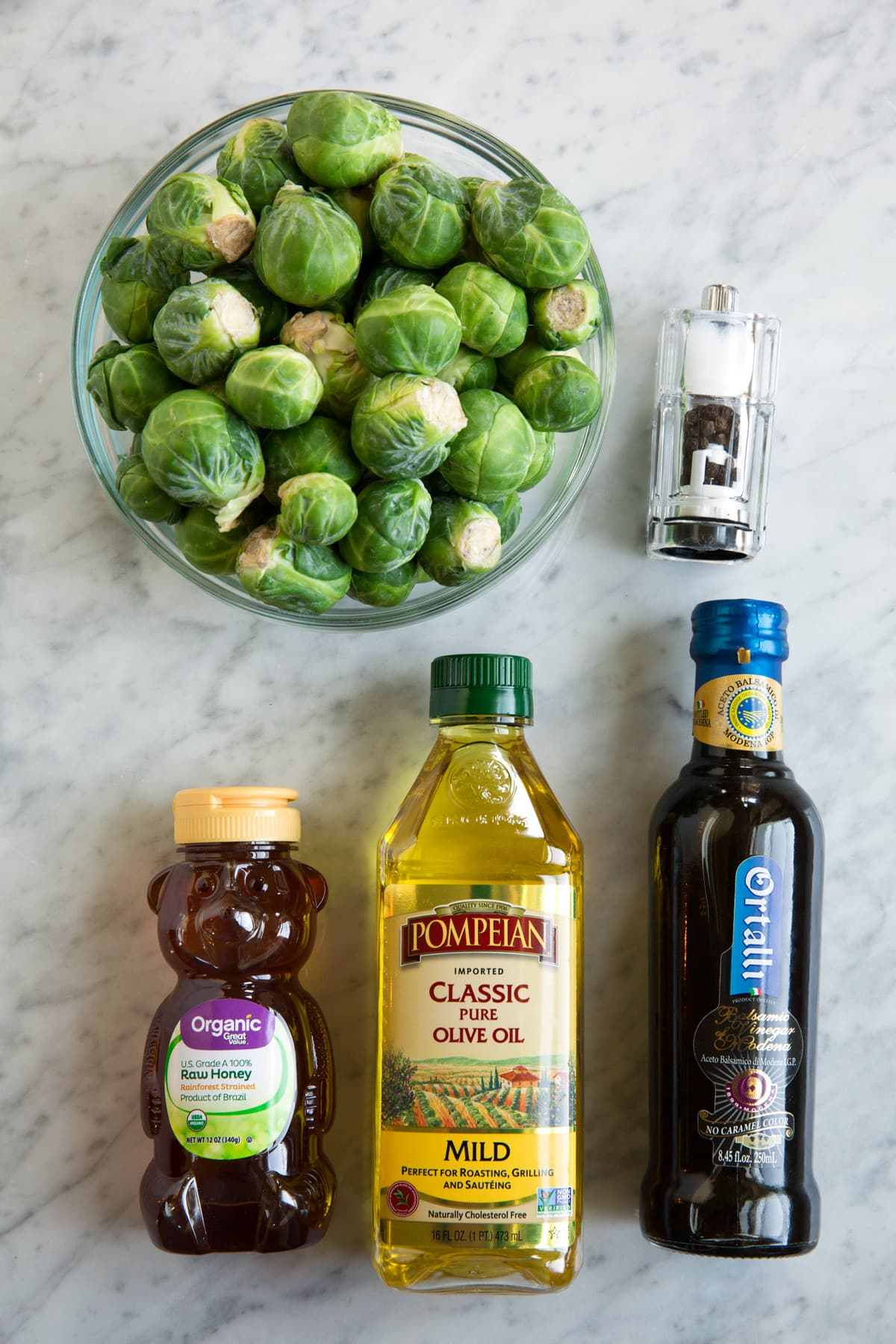 Roasted Brussels Sprouts with Balsamic and Honey ingredients needed shown here on a white marble surface