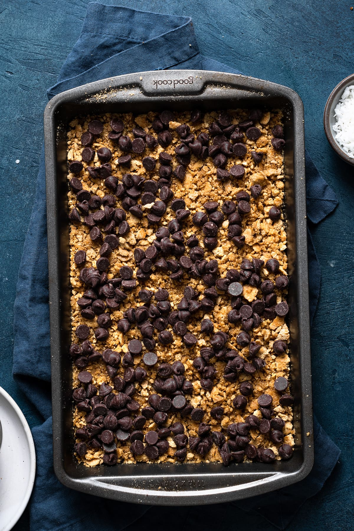 Showing how to make magic 7 layer bars. Sprinkling chocolate chips over graham cracker layer in baking dish.