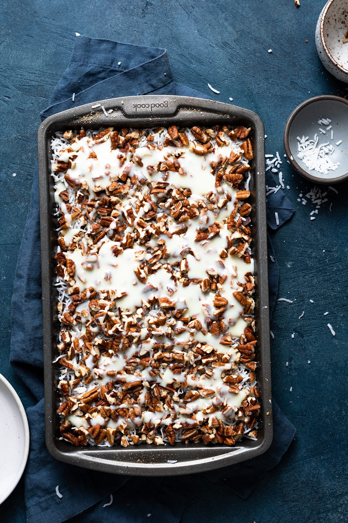 Showing how to make magic bars pouring sweetened condensed milk over chocolate chip layer in baking dish.