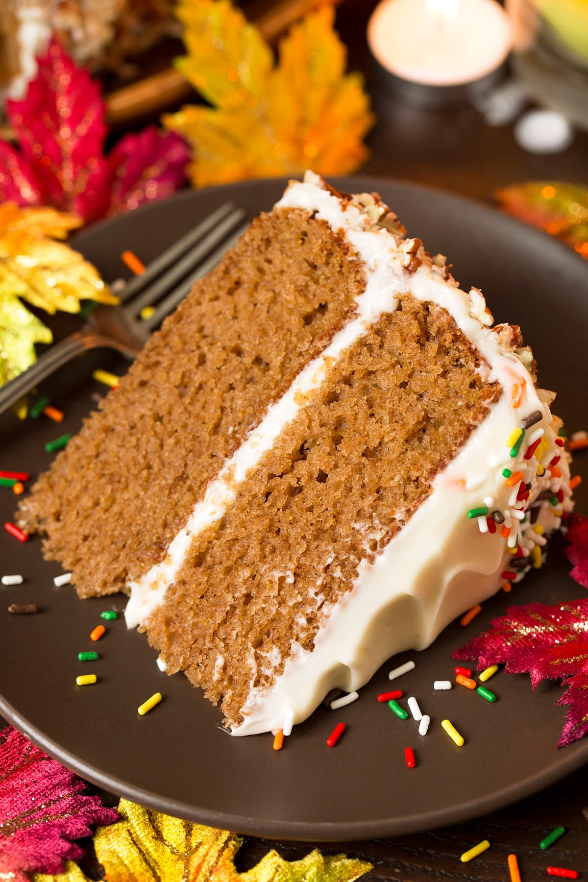 Spice Cake slice with cream cheese frosting, on a brown matte plate decorated with colorful fall leaves around it.