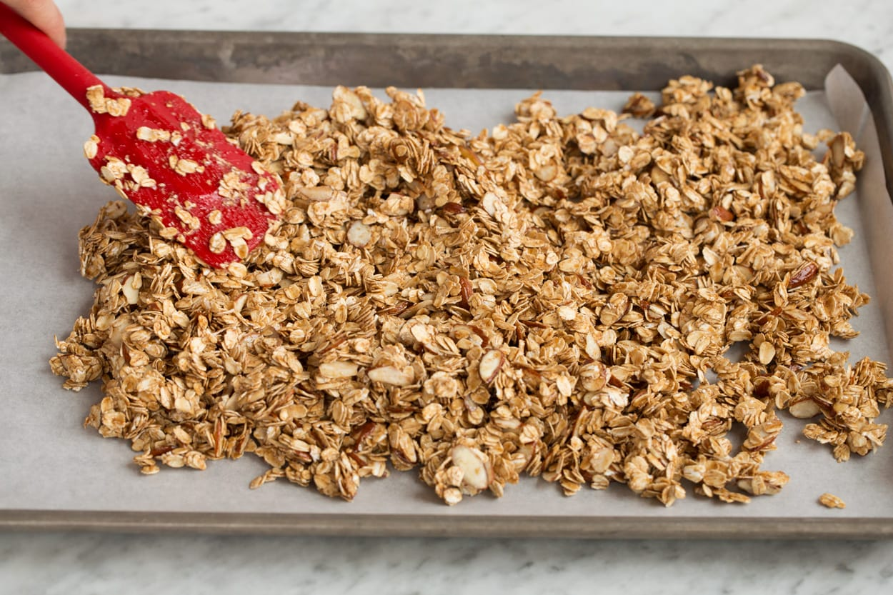 Spreading granola mixture on parchment paper lined baking sheet to bake.