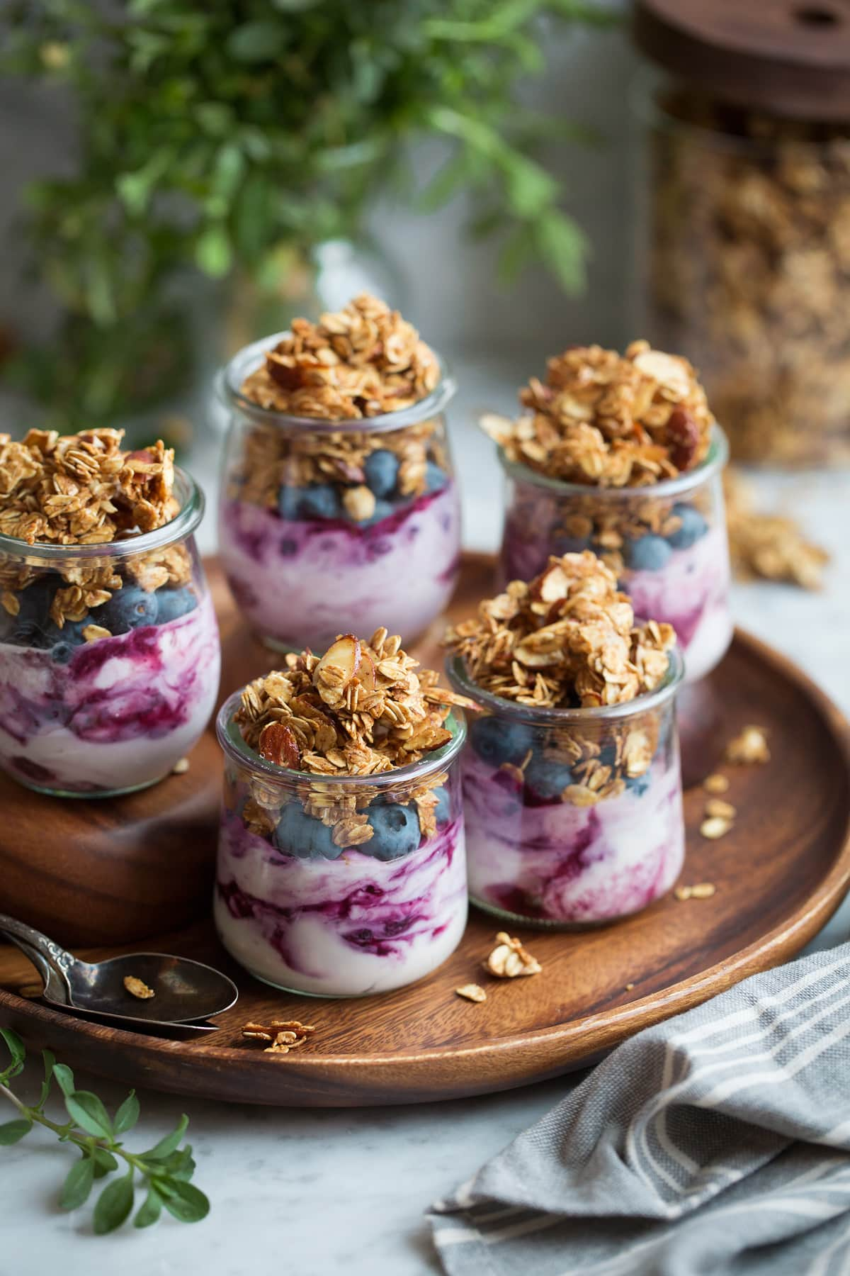 Five servings of granola, yogurt and berries in glass jars.