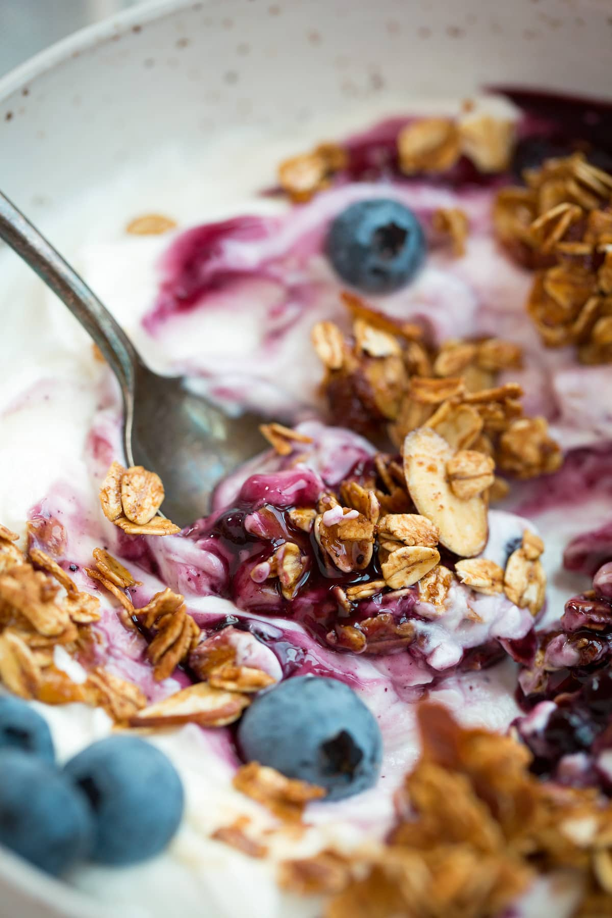 Close up image of granola with yogurt, berries and blueberry sauce.