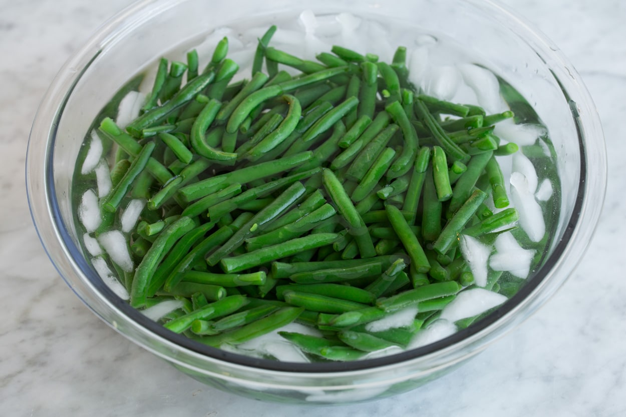 Green beans in an ice water in a glass bowl after draining.