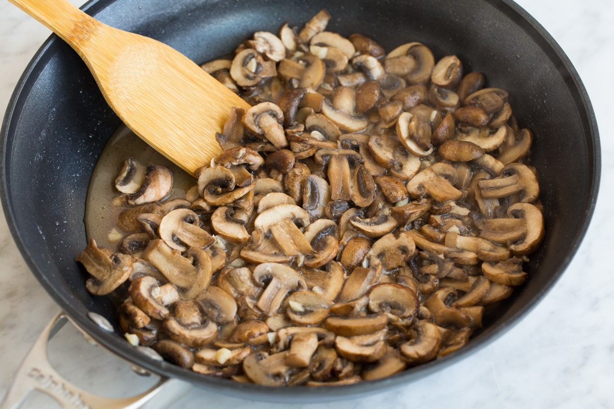 Sauteeing mushrooms in a large dark non-stick skillet for green bean casserole.