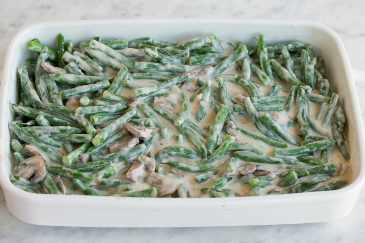 Creamy coated green beans and mushrooms in a white ceramic baking dish before baking, for Green Bean Casserole.