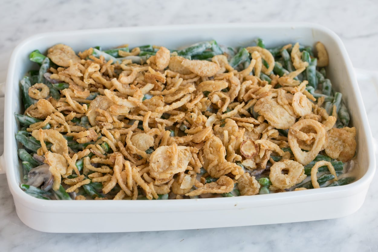 Adding crispy fried onions to Green Bean Casserole before baking.