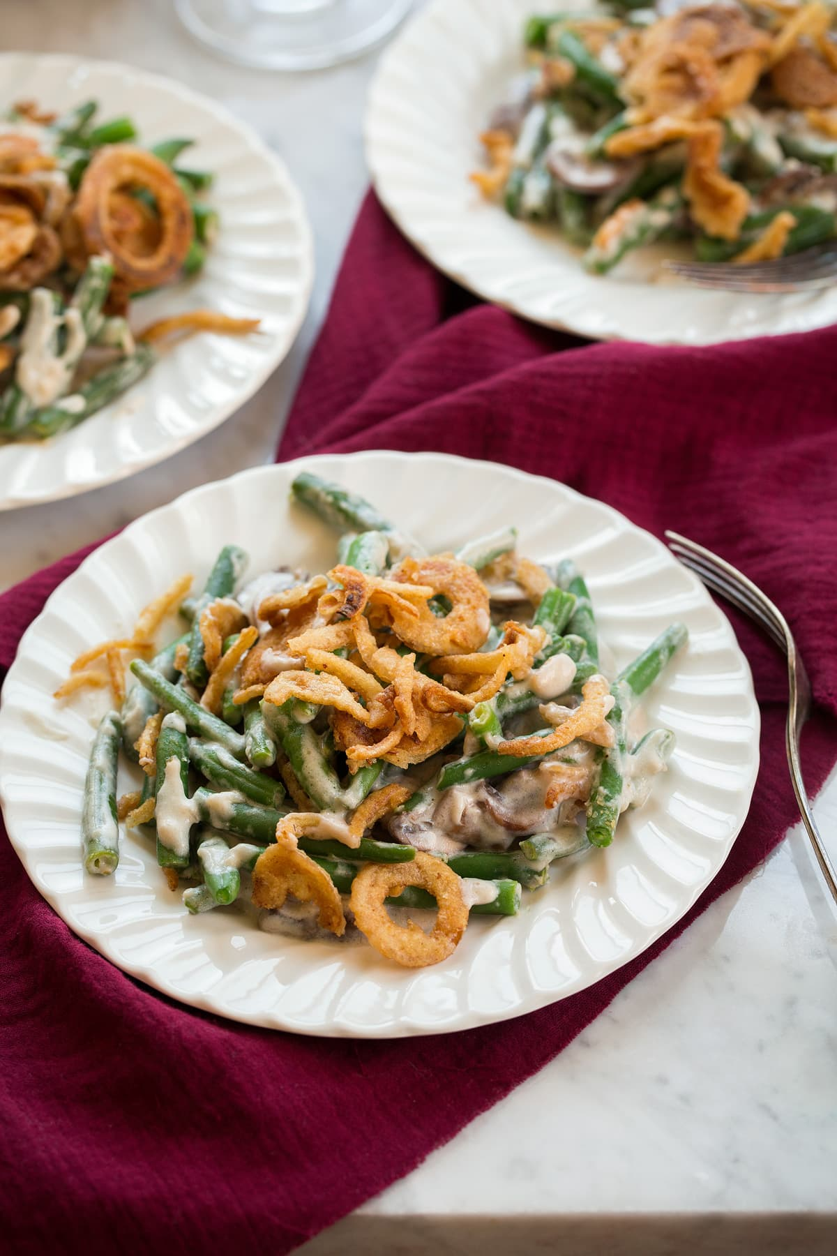 Three individual servings of Green Bean Casserole on white scalloped salad plates.