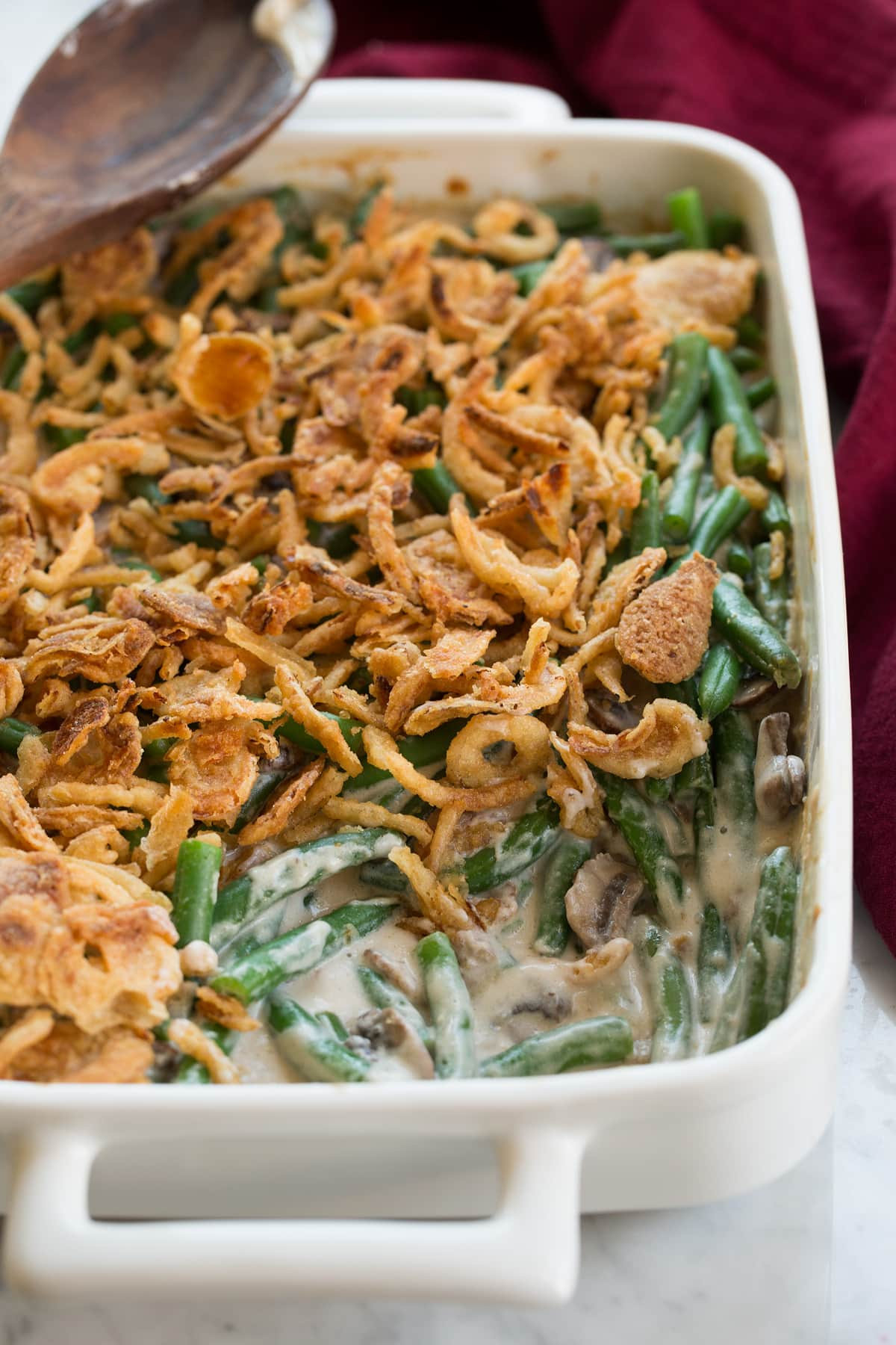 Green Bean Casserole in a white ceramic baking dish with a scoop removed to show filling.