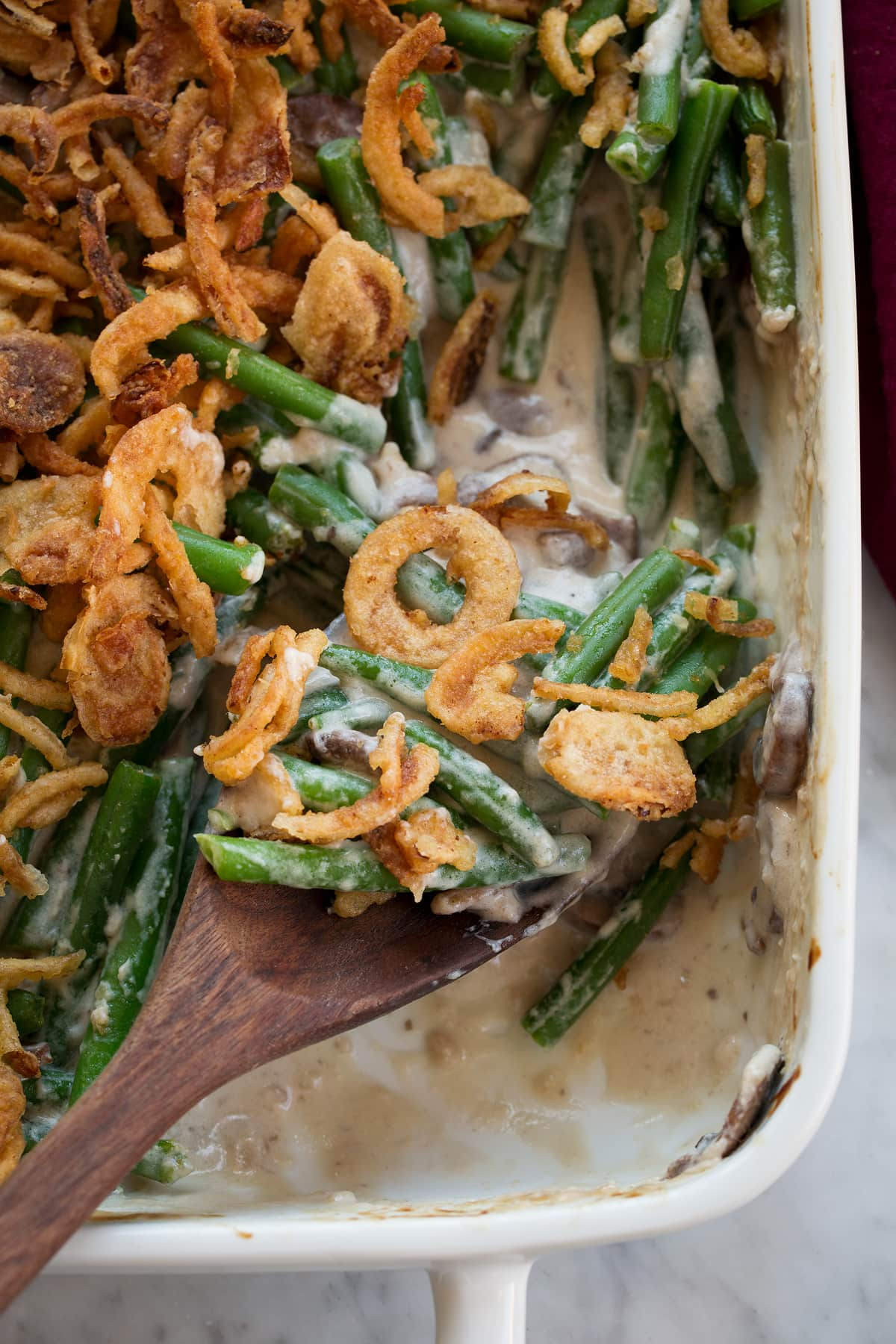 Close up image of scoop of green bean casserole on a wooden spoon.