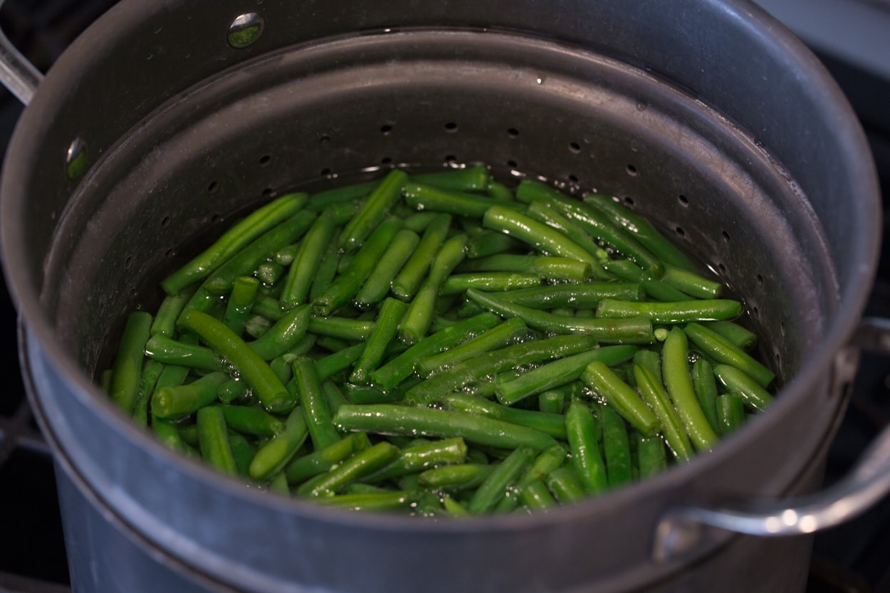 Showing how to make green bean casserole. Start by boiling green beens in pot of water.