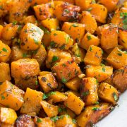 Roasted butternut squash with garlic and fresh herbs in a white ceramic serving bowl set over a white marble surface.