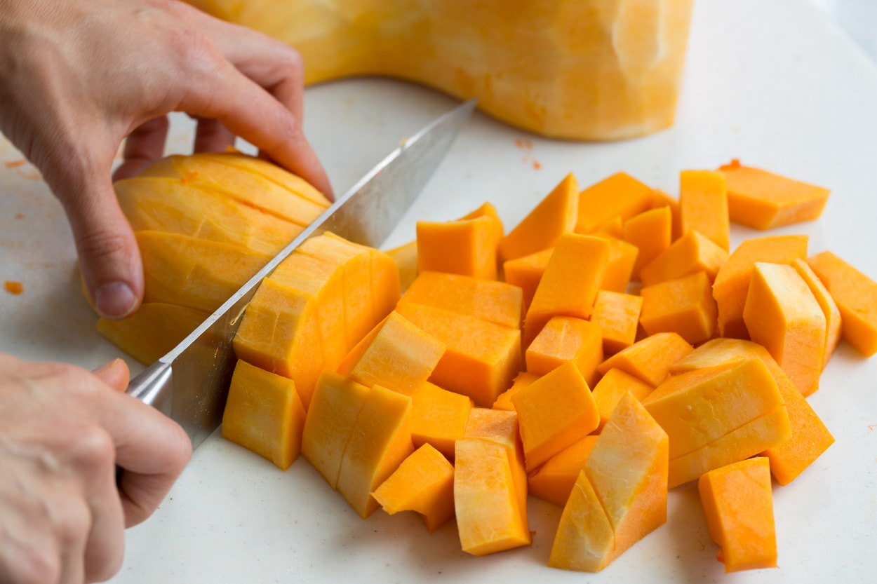 Showing how to cut a whole butternut squash into cubes on a cutting board with a knife.