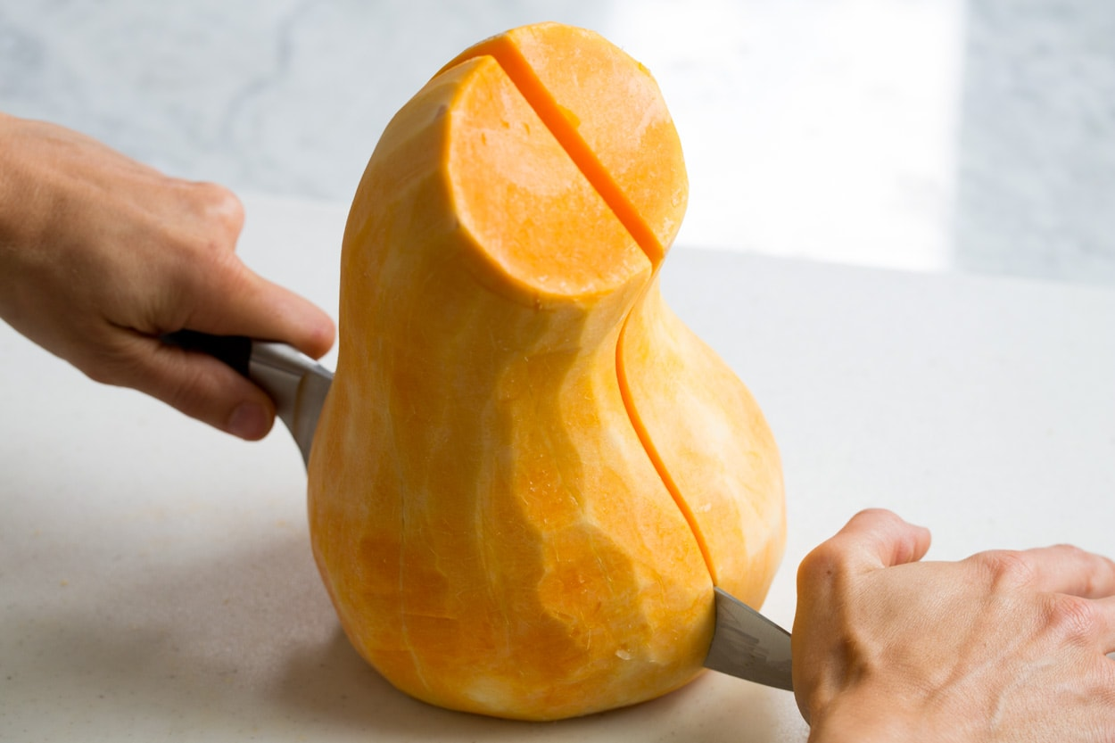 Showing how to halve a butternut squash on a cutting board.