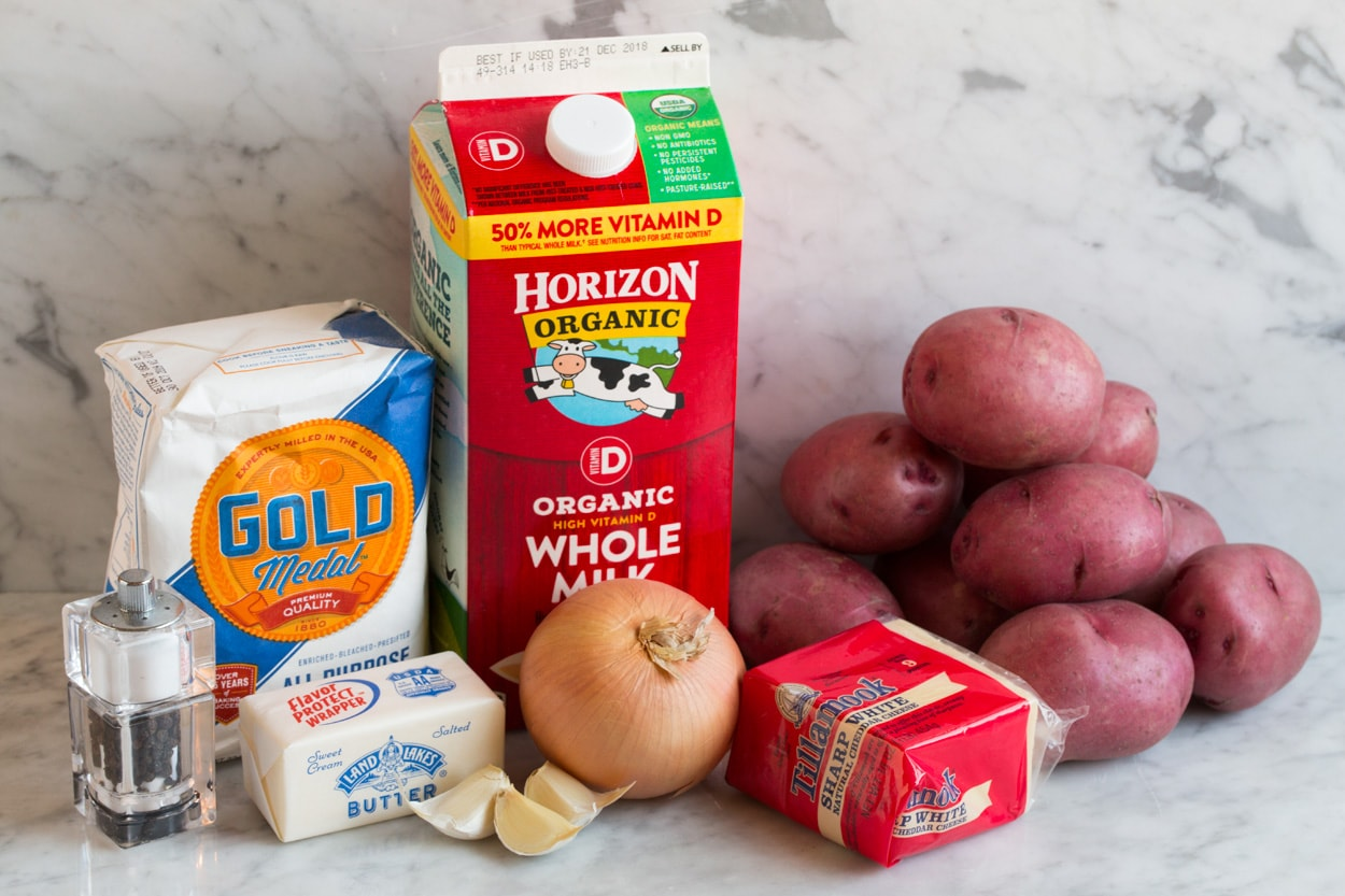 Ingredients for scalloped potatoes shown here including whole milk, butter, flour, onion, garlic, red potatoes, sharp white cheddar cheese, salt and pepper.
