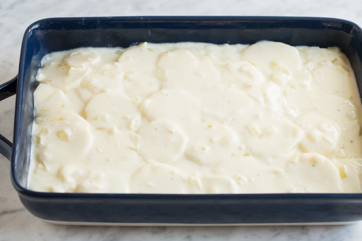 Finishing scalloped potatoes by adding a final layer of sauce over thinly sliced potatoes in baking dish.