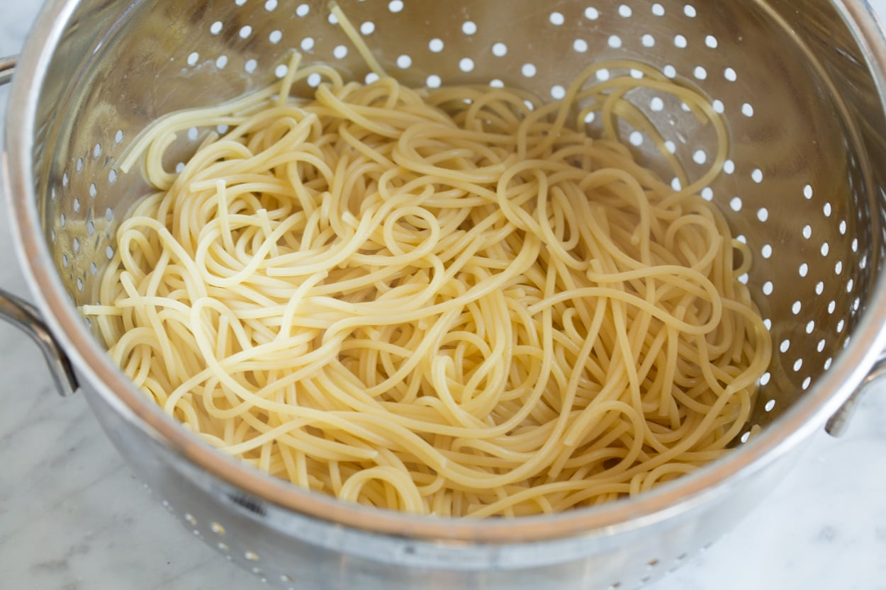 cooked spaghetti noodles in metal colander