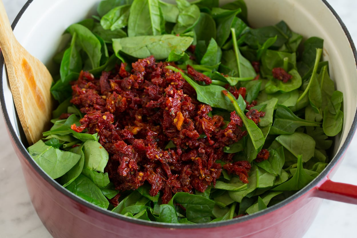 chopped sun dried tomatoes and fresh spinach in large pot