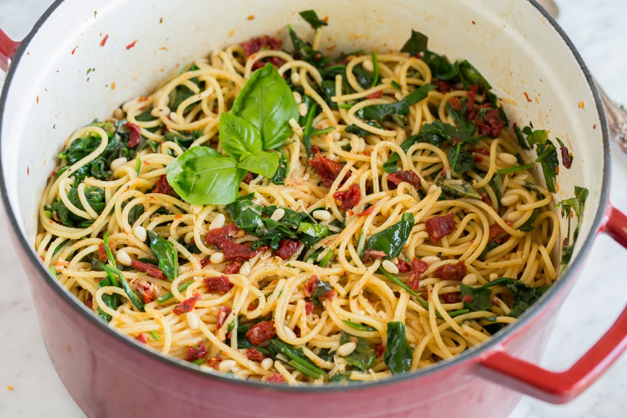 sun dried tomato pasta garnished with fresh basil in large pot