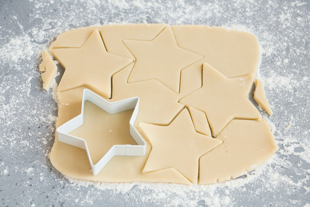 Cutting star shapes from cookie dough for stained glass cookies.