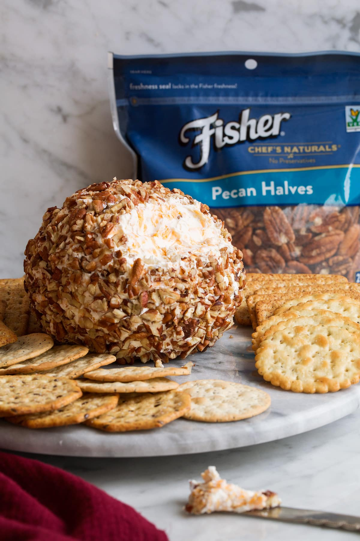 Cheese ball on a serving plate with crackers.