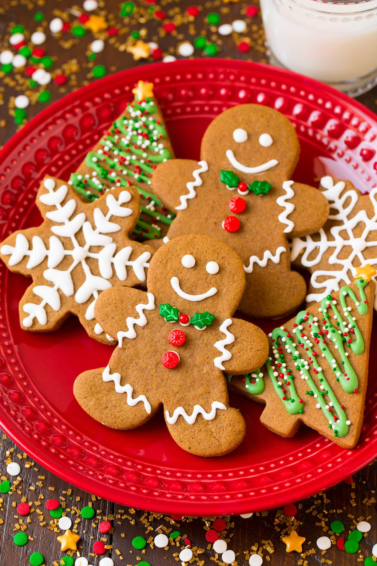 Gingerbread men cookies and trees and snowflakes on a red plate surrounded by Christmas sprinkles.