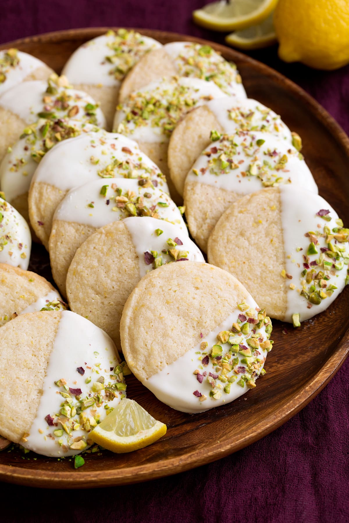 Shortbread cookies with lemon flavor that are dipped in white chocolate and sprinkled with pistachios. Shown here on a wooden serving plate.