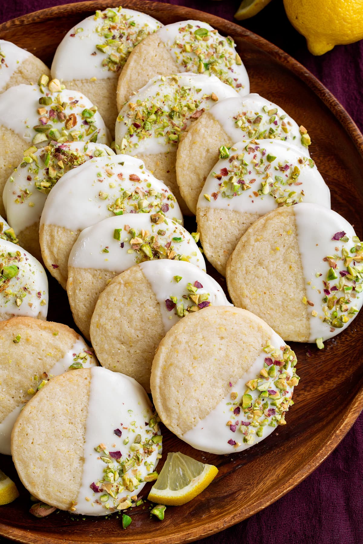 Shortbread cookies on a wooden serving plate. Flavored with lemon, white chocolate and pistachios.