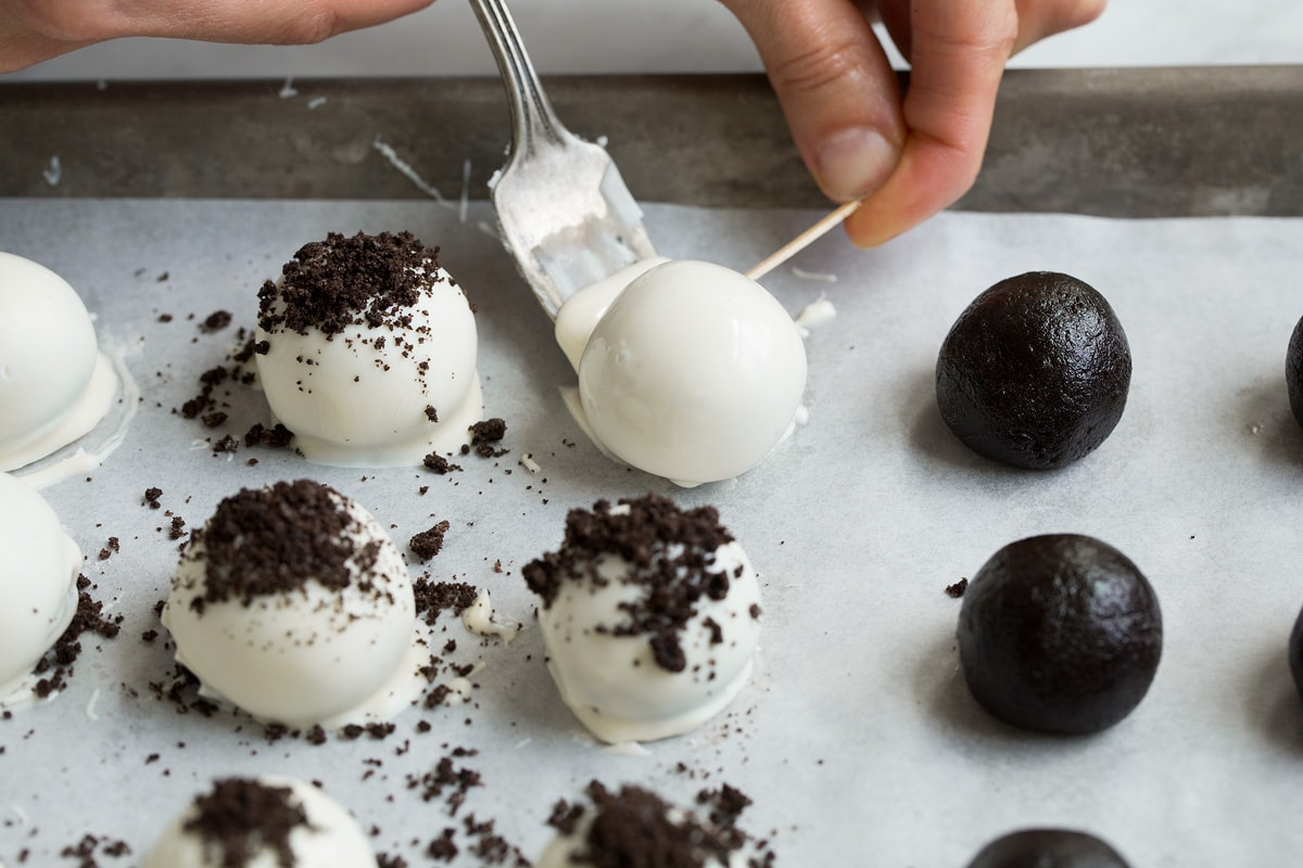 Transferring dipped oreo ball to parchment paper using a fork and toothpick.