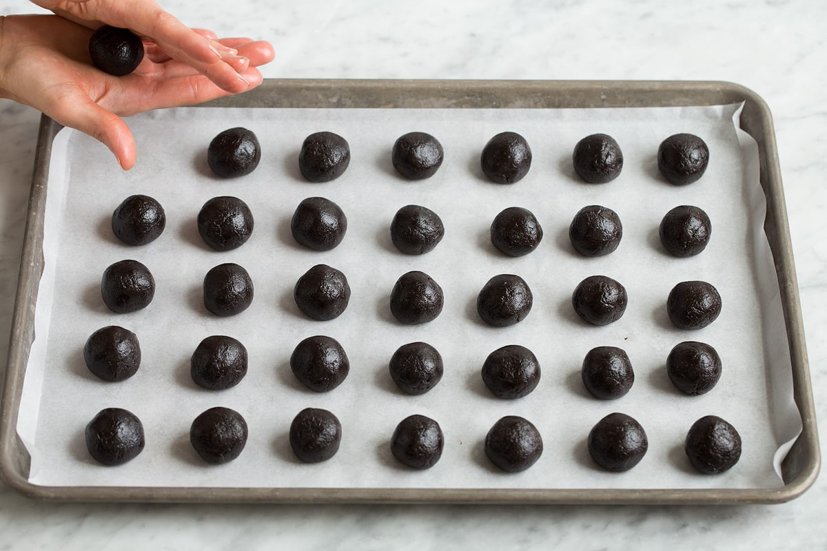 Uniform rolled oreo balls on a baking sheet.
