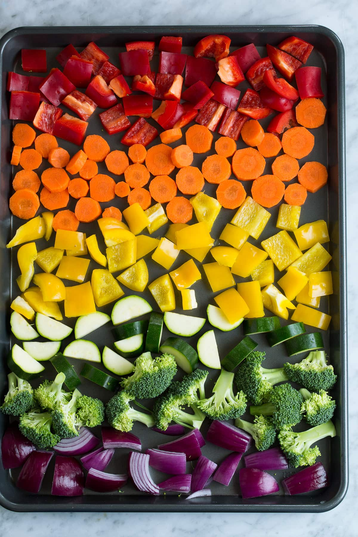 Diced vegetables on a baking sheet before oven baking.