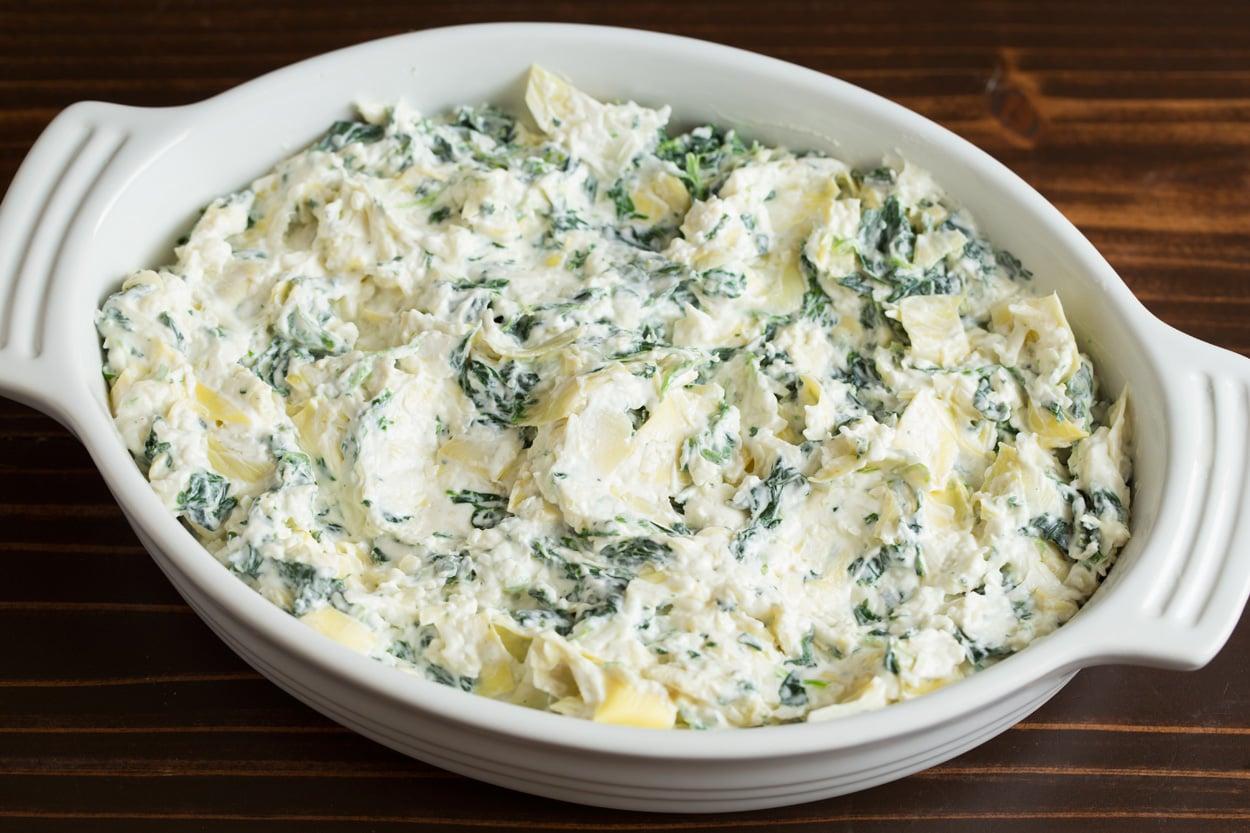 Spreading Spinach Artichoke Dip mixture into small casserole dish.