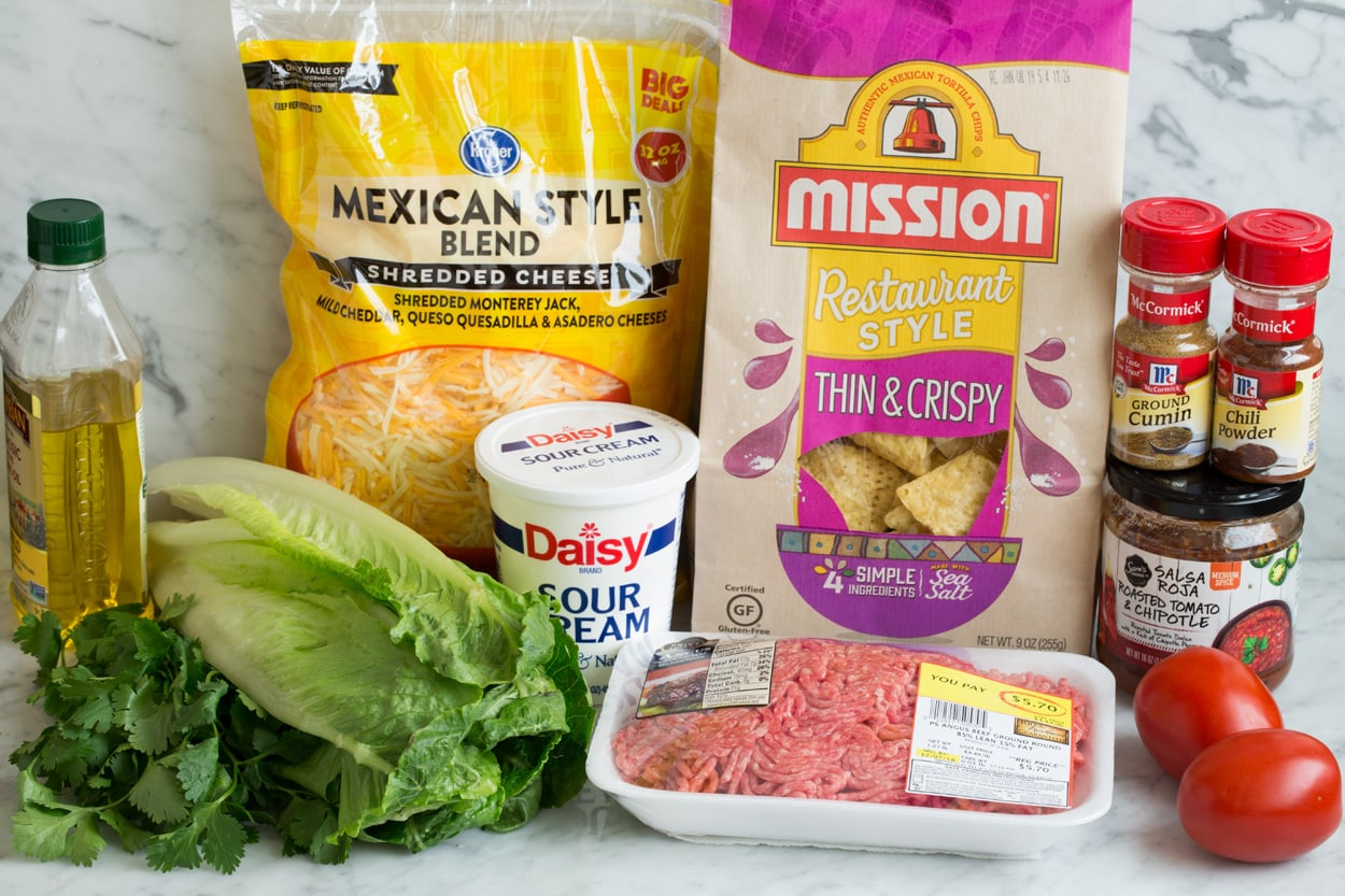 Image showing ingredients needed for taco salad including ground beef, olive oil, spices, bottled salsa, chips, cheese, sour cream, tomatoes.