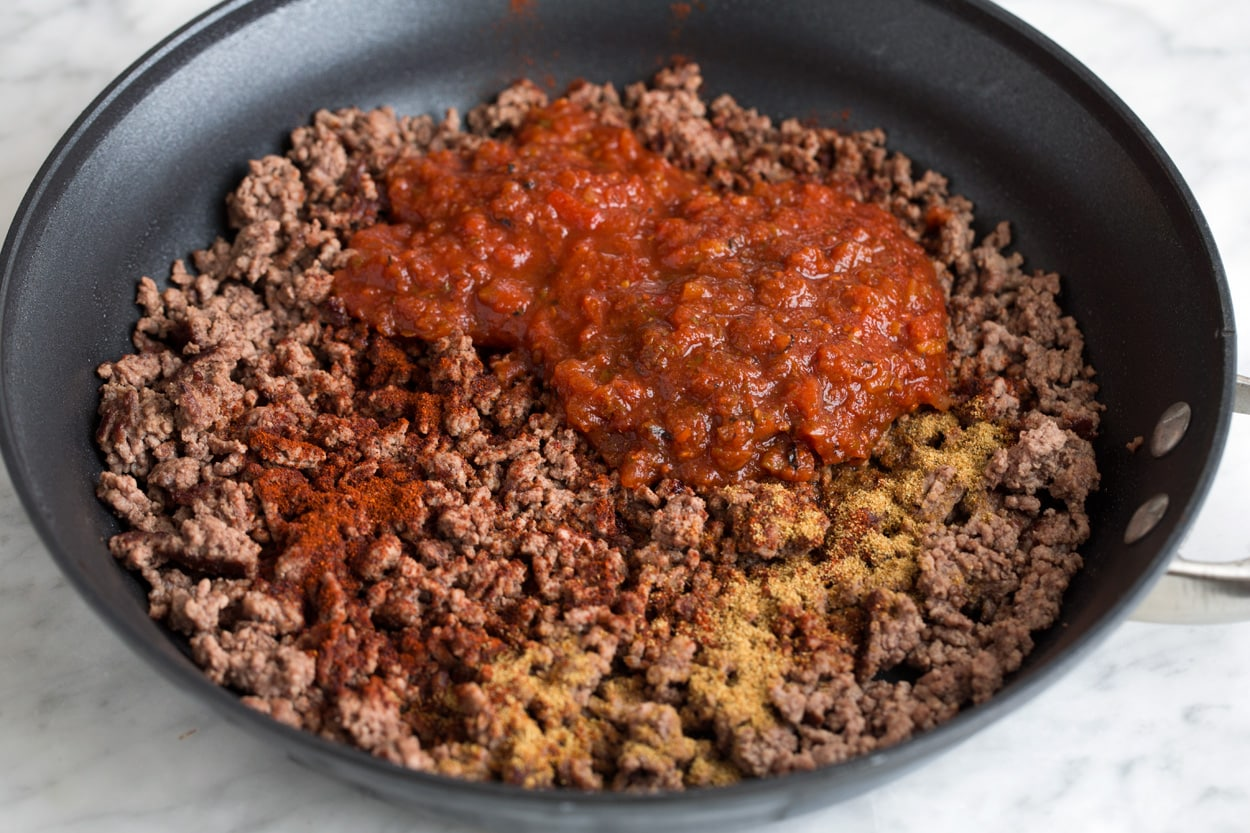 Adding salsa and spices to cooked ground beef mixture in large skillet.