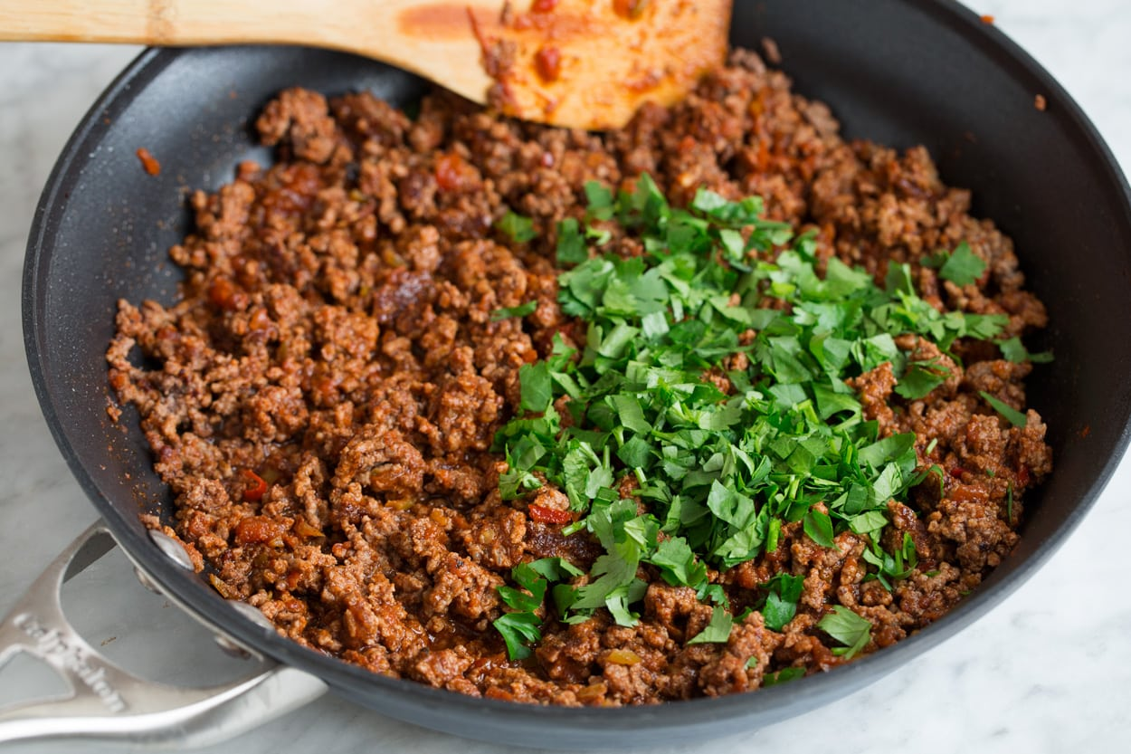 Adding cilantro to finished taco salad beef mixture in skillet.