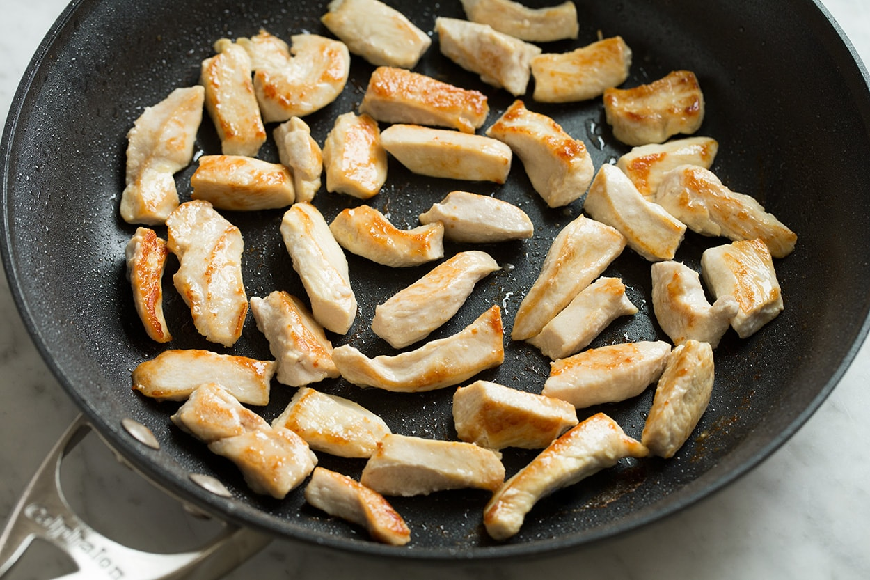 Searing pieces chicken in skillet for chow mein.