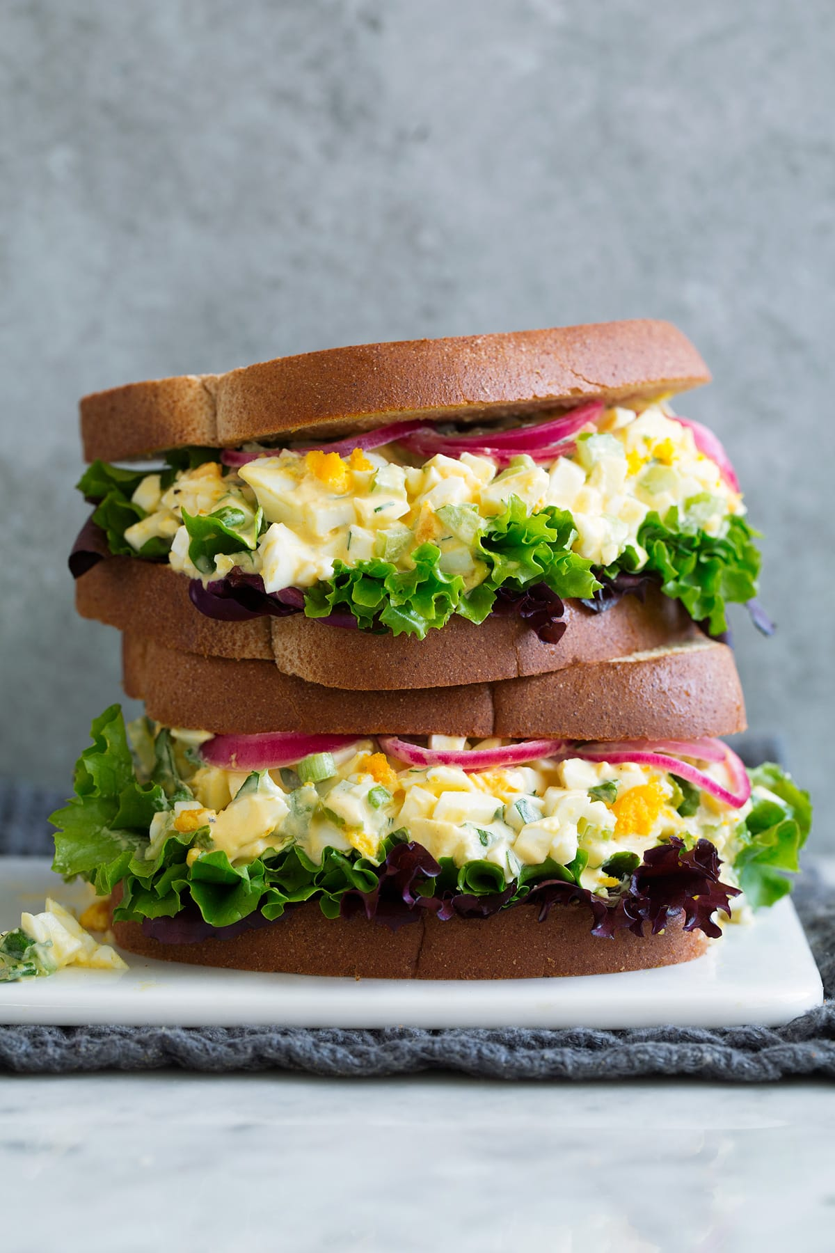 Stack of two Egg Salad Sandwiches on a white serving platter sitting on marble with a grey background.
