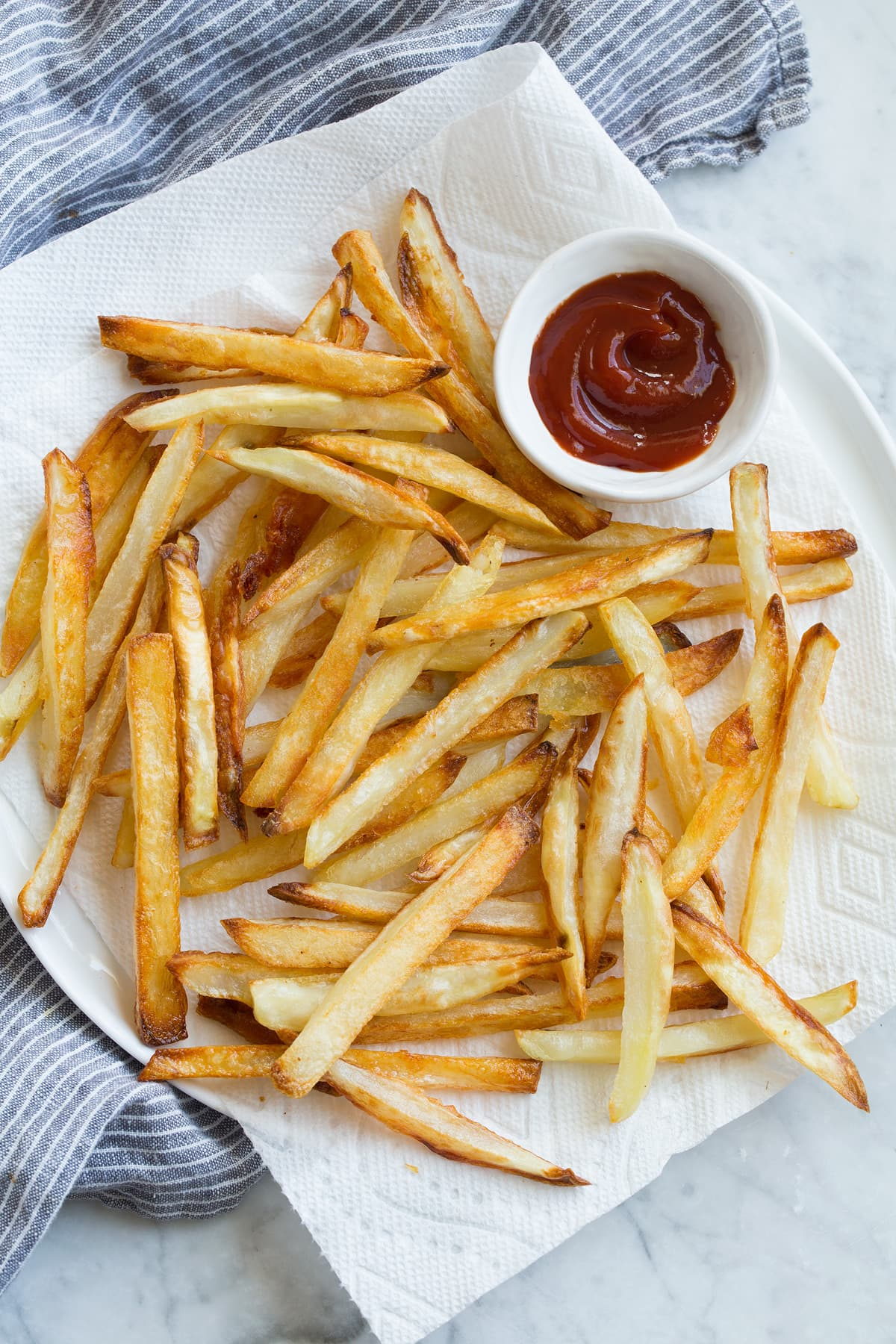French Fries on a napkin lined plate with a side of ketchup.