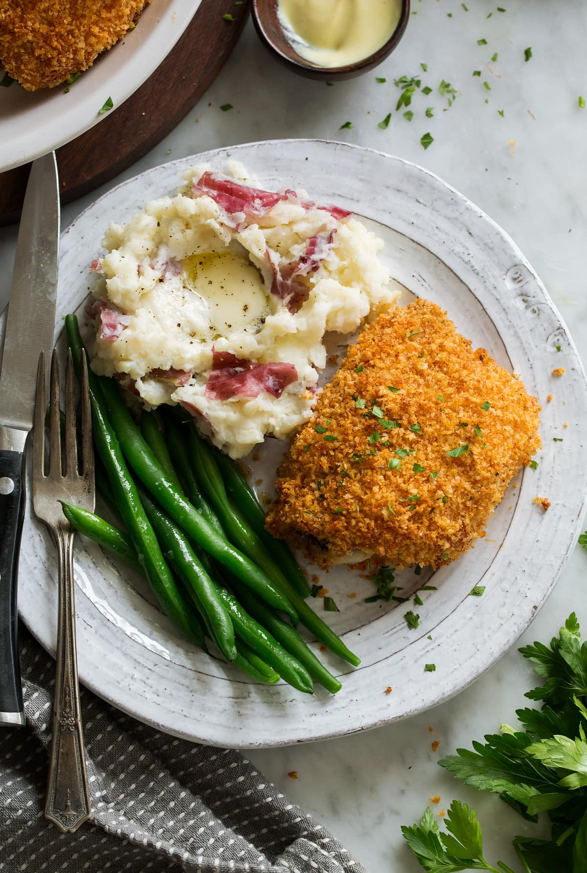 Oven Fried Chicken on serving plate with a side of mashed potatoes and green beans.