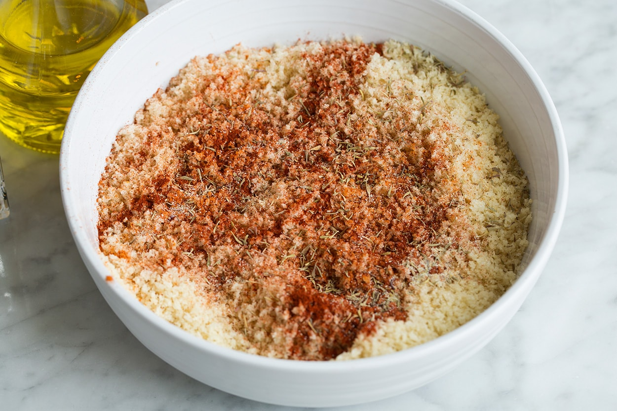 Mixing panko with olive oil and spices in a shallow dish for oven fried chicken.