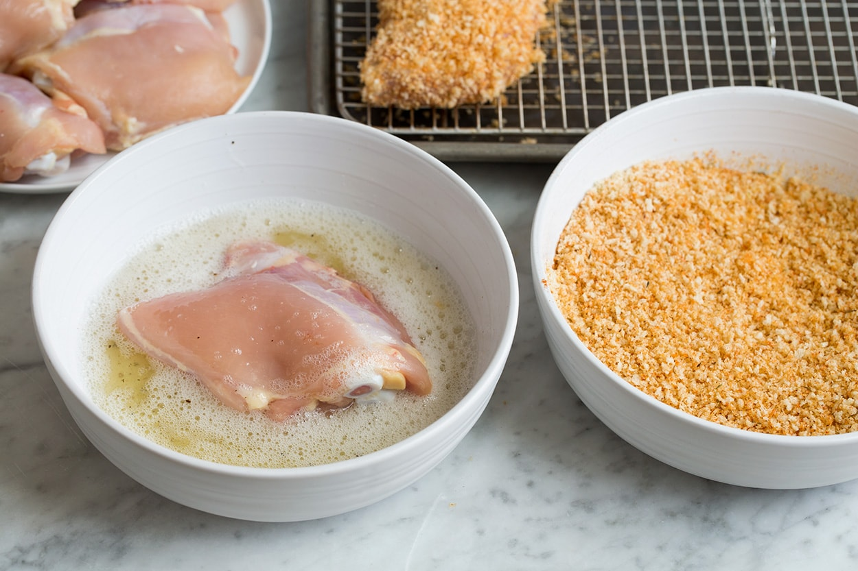 Dressing chicken thigh in egg white in a bowl and panko for Oven Fried Chicken
