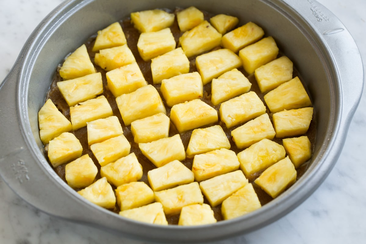 Adding fresh pineapple chunks over brown sugar layer in cake pan.